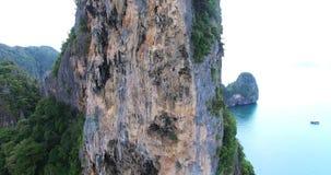 De mensen beklimmen de tropische rots in het overzees Mening van de tropische oceaan en groene bergen Krabi thailand stock video