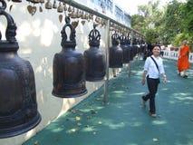 De mensen bellen klokken bij het gouden onderstel in Bangkok. Royalty-vrije Stock Foto