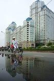 De mensen berijden fiets met high-rise de bouwachtergrond Stock Afbeelding