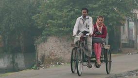 De mensen berijden fietsen door de straat op een koude mistige ochtend in Puthia, Bangladesh stock videobeelden