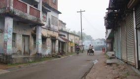 De mensen berijden fietsen door de straat op een koude mistige ochtend in Puthia, Bangladesh stock video