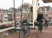 De mensen berijden fietsen op een brug in Amsterdam stock foto's