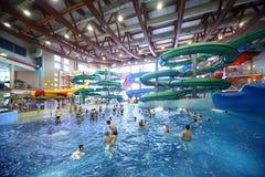 De mensen berijden op hellingen en zwemmen in pool Royalty-vrije Stock Fotografie