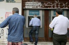 De mensen bevinden zich in een rij om ATMs van een bank te gebruiken stock foto