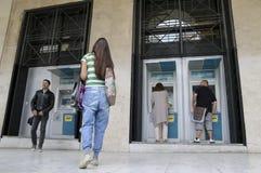 De mensen bevinden zich in een rij om ATMs van een bank te gebruiken stock afbeelding
