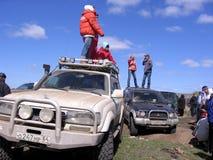De mensen bevinden zich op het dak van de jeeps rennend SUVs-menigte van toeschouwers die op een geplakte auto letten ontslaand v royalty-vrije stock afbeelding