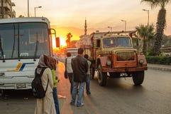 De mensen bevinden zich op weg dichtbij bus bij zonsondergang Stock Fotografie