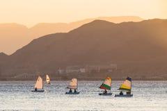 De mensen bewegen zich in boten met een zeil en het windsurfing in het Rode Overzees Achtergrond - de bergen stock fotografie