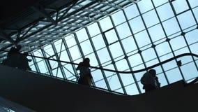 De mensen bewegen zich op een roltrap in een gebouw stock footage