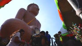 De mensen bidden en zetten gouden stuk bij het Grote standbeeld van Boedha stock videobeelden