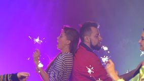 De mensen bij de club steken de sterretjes aan die zij in disco hebben gevierd Rook achtergrond Langzame Motie stock footage