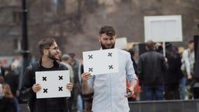 De mensen bij de manifestatie met banners bekijken de telefoon Glimlachende mens en mobiele telefoon stock videobeelden