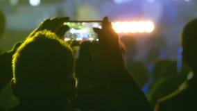 De mensen bij Muziek schommelen Overleg die Foto's nemen of Video met Smartphones registreren stock footage