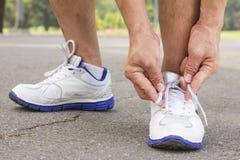 De mensen bindt schoenenkant voor jogging bij park Stock Foto