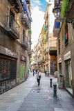 De mensen binnen alleyway/versmallen baksteenstraat van winkels en huizen in Barcelona royalty-vrije stock fotografie