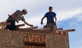 De mensen bouwen dak voor huis voor Habitat voor het Mensdom Stock Afbeeldingen