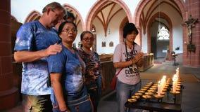 De mensen branden kaars voor herinneren zich en het bidden eerbied aan god bij St Gallus kerk stock footage