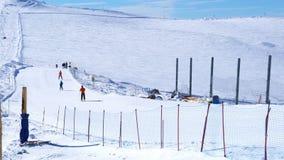 De mensen die bij de ski ski?en nemen op Klein Matterhorn in Zermatt-Dorp zijn toevlucht stock videobeelden