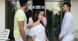 De mensen die binnen van de zomerterras lopen die, de vrienden van het mengelingsras groeperen mededeling in hotel in tropisch bo stock videobeelden