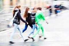 De mensen die de straat kruisen til het regenen Stock Fotografie