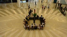 De mensen die en wachten bij vergaderingspunt en mensen en gebruiksroltrap die lopen zitten stock videobeelden