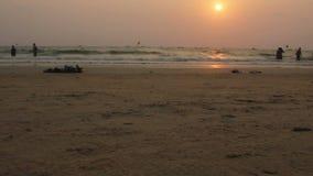 De mensen die langs op lopen slaan tijdens Zonsondergang in Goa, Bhaga-strand stock video