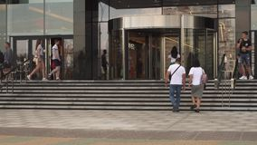 De mensen die langs stadsstraat lopen, gaan in en uit winkelcomplex op de zomerdag stock video