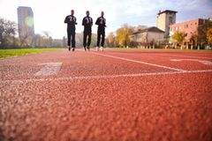 De mensen die op atletiek lopen volgen stegen stock foto