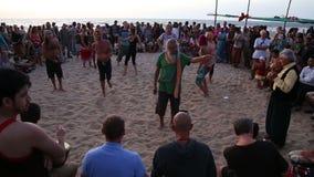 De mensen die op een zandig strand aan de muziek dansen die door djembe wordt gespeeld verbinden stock videobeelden