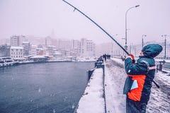 de mensen die op galata vissen overbruggen op een sneeuwdag in de winter stock afbeelding