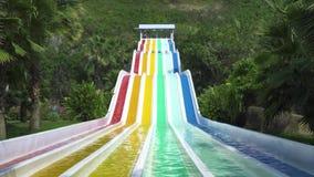 De mensen die op kleurrijk water glijden glijden bij aquapark bij de zomervakantie Mensen die pret hebben die op dia's in vermaak stock videobeelden