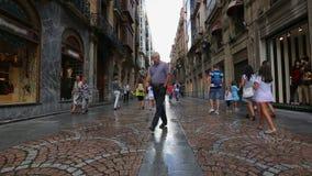 De mensen die op smalle straten met aantrekkelijk glas lopen winkelen vensters in Bilbao stock footage
