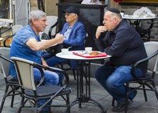 De mensen die in openlucht een rond kleine lijst het drinken koffie zitten bij retaurant in Mahane Yehuda behandelden straatmarkt royalty-vrije stock afbeeldingen