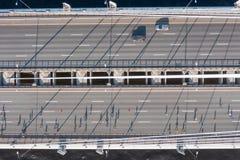 De mensen die over de brug in werking worden gesteld, de schaduwen op de asfaltwegen zijn zichtbaar van bovengenoemd satellietbee stock foto