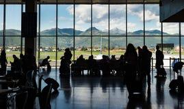 De mensen die van de silhouetmenigte op vliegtuig in terminal met bergachtergrond wachten Stock Afbeeldingen