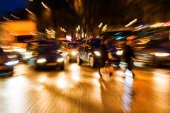 De mensen die van het gezoembeeld een straat kruisen bij nacht Stock Fotografie