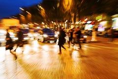 De mensen die van het gezoembeeld een straat kruisen bij nacht Royalty-vrije Stock Afbeelding