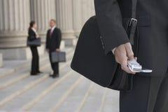 De Mensen die van zakenmanusing cellphone and op Achtergrond spreken stock afbeelding
