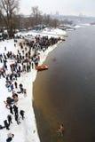 De mensen dompelen in ijzig water onder tijdens Epiphany-viering Stock Afbeelding