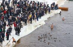 De mensen dompelen in ijzig water onder tijdens Epiphany-viering Stock Fotografie