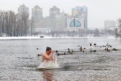 De mensen dompelen in ijzig water onder tijdens Epiphany-viering Royalty-vrije Stock Fotografie