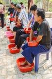 De mensen doorweken hun handen en voeten met kruidenwater voor sk Stock Fotografie