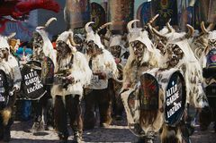 De mensen dragen kostuums en maskers en spelen muziek bij de straat tijdens Carnaval in Luzerne, Zwitserland Stock Afbeeldingen