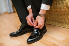 De mensen dragen schoenen en treffen voor huwelijk voorbereidingen het sluiten mannelijke schoenveters stock afbeeldingen