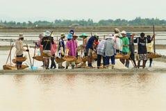 De mensen dragen zout bij het zoute landbouwbedrijf in Huahin, Thailand stock fotografie