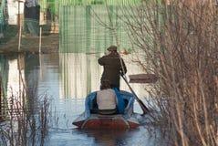De mensen in een boot varen langs een overstroomde straat aan hun huis Gedaald onder het bezit van de straathuizen van de waterom Stock Afbeelding