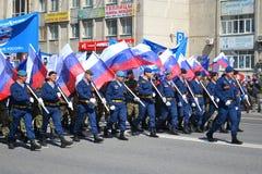De mensen in eenvormig met vlaggen van de Russische Federatie nemen deel Royalty-vrije Stock Afbeeldingen