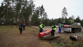De mensen in eenvormige redding dragen oranje tent in bosvrachtwagen Emercom het kamperen stock footage