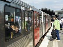 De mensen gaan de trein bij Baumwall-Post in Hamburg in Stock Foto