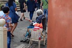 De mensen gaan door Etnische oude vrouwenzitting over op de doos van de Kerstmisgift van de rolstoelholding bedelend voor aalmoes royalty-vrije stock foto's